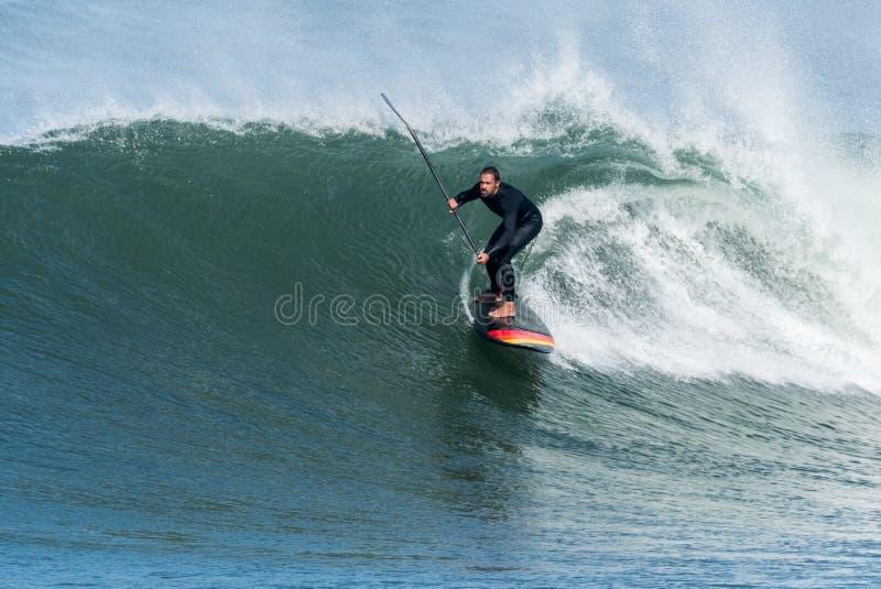 Lev?ntese a la persona que practica surf de la paleta imagenes de archivo