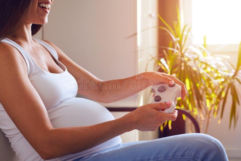Leva di comando della tenuta della donna incinta e video giochi di gioco fotografia stock libera da diritti