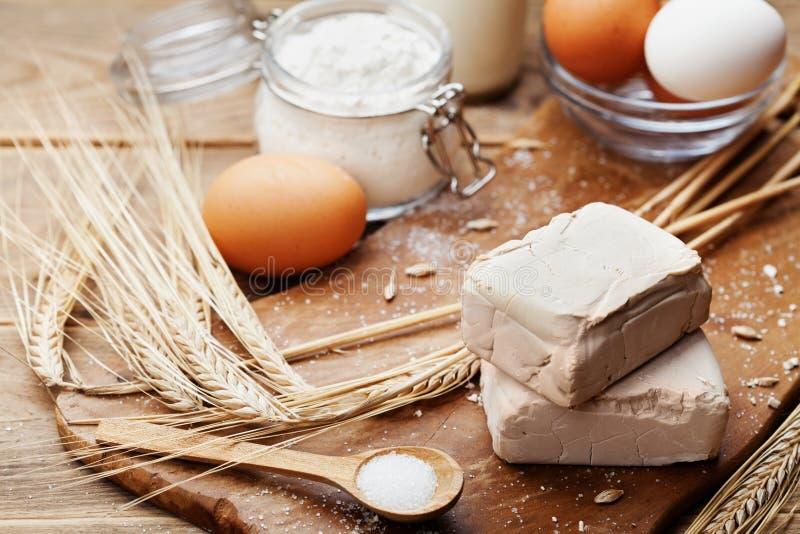 Levadura e ingredientes frescos para la hornada de Pascua en fondo rústico de la cocina fotos de archivo