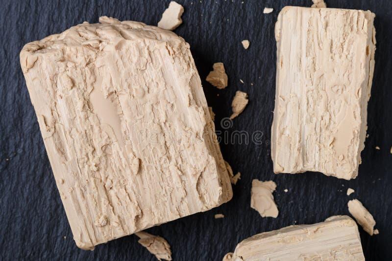 Levadura fresca en el primer gris de la tabla Ingrediente para los productos del pan que cuecen y de la panadería fotografía de archivo libre de regalías