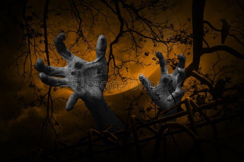 Levande dödhand som stiger ut från det gamla staketet över det döda trädet, galande, måne royaltyfri bild