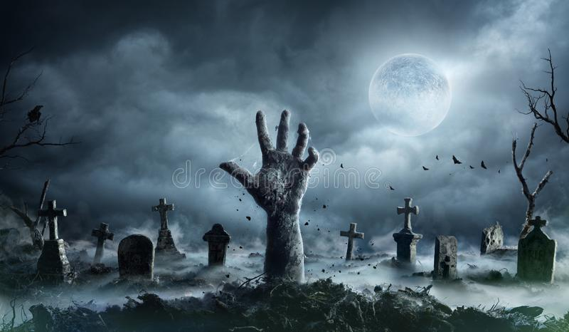 Levande dödhandresning ut ur en kyrkogård arkivfoto