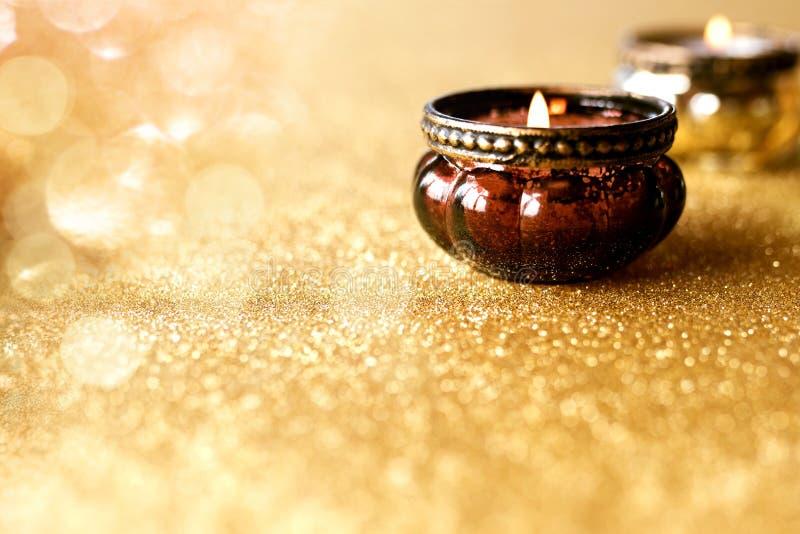 Levande ljus på guld- blänka bakgrund royaltyfri foto