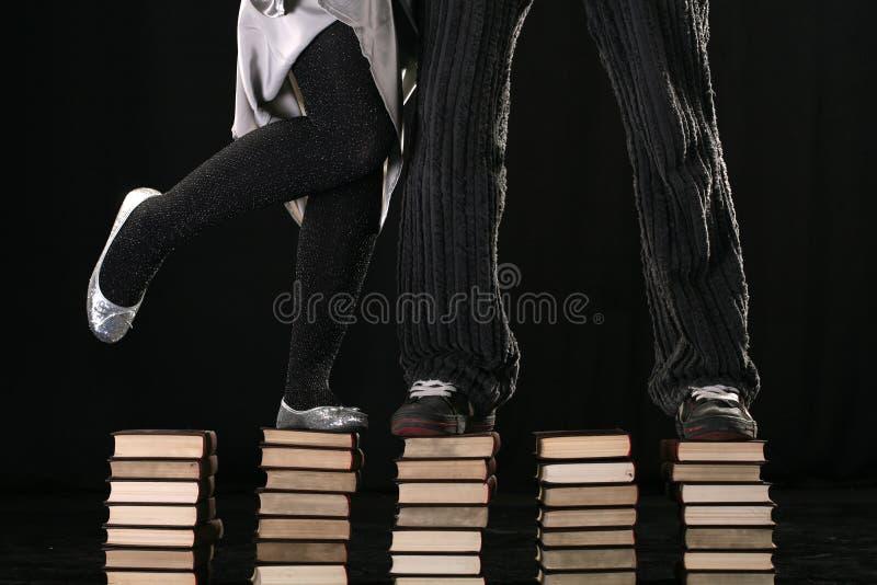 Levandosi in piedi sui libri insieme fotografia stock