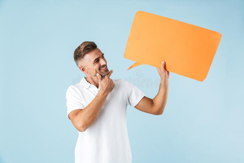 Levantamento adulto emocional entusiasmado do homem isolado sobre o fundo azul da parede que guarda a bolha do discurso fotografia de stock royalty free
