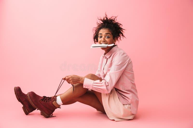 Levantamento africano novo bonito da mulher isolado sobre as sapatas vestindo do fundo cor-de-rosa da parede que guardam o passap imagem de stock royalty free