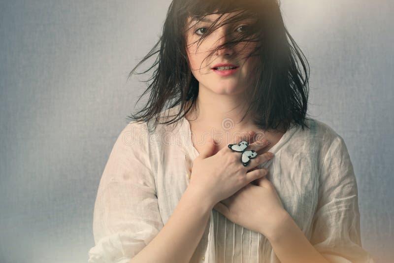 Levantamento atrativo da mulher nova Anel de dedo da borboleta imagem de stock royalty free