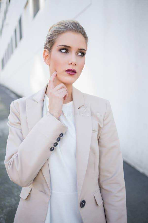 Levantamento atrativo pensativo da mulher de negócios imagens de stock royalty free