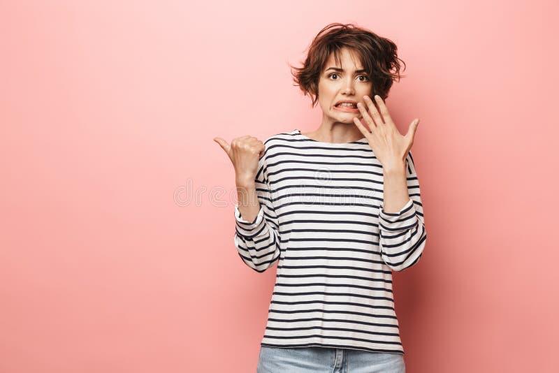 Levantamento bonito chocado confuso da mulher isolado sobre apontar cor-de-rosa do fundo da parede fotografia de stock