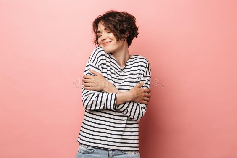 Levantamento bonito feliz da mulher isolado sobre o fundo cor-de-rosa da parede fotografia de stock