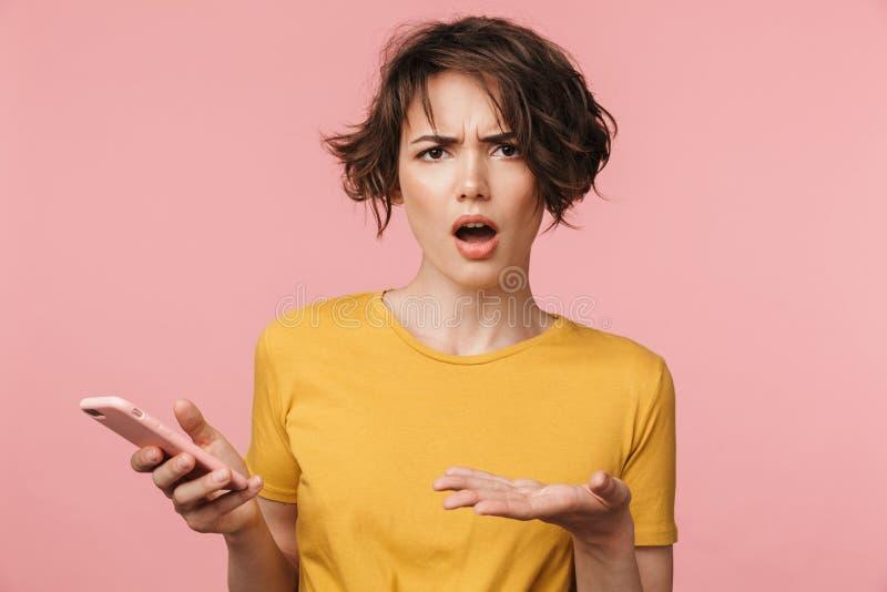 Levantamento bonito novo chocado da mulher isolado sobre o fundo cor-de-rosa da parede usando o telefone celular fotografia de stock