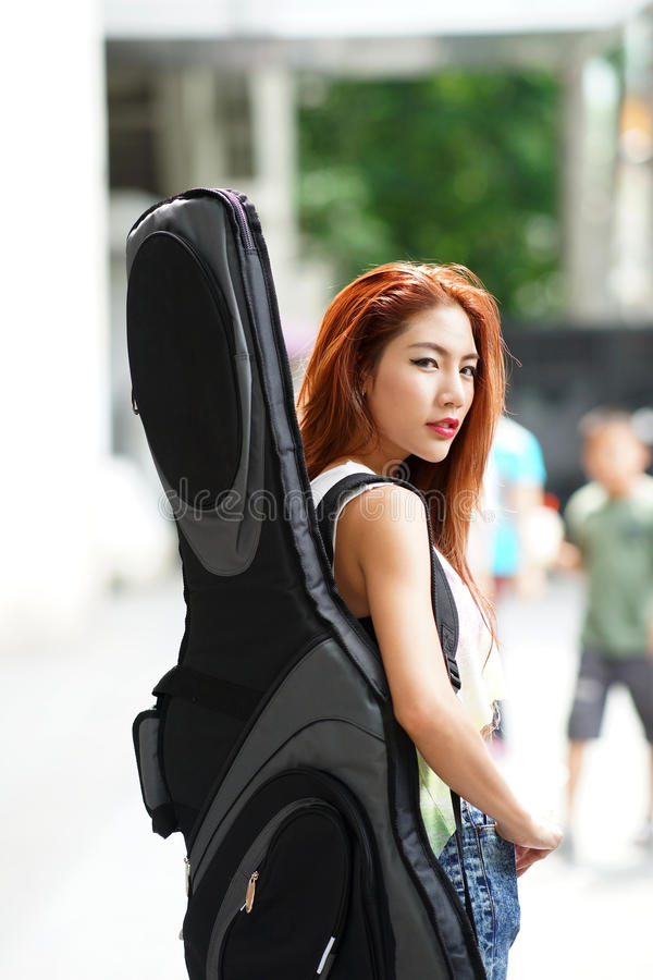 Levantamento bonito novo da mulher exterior com seu saco da atuação da guitarra fotos de stock royalty free