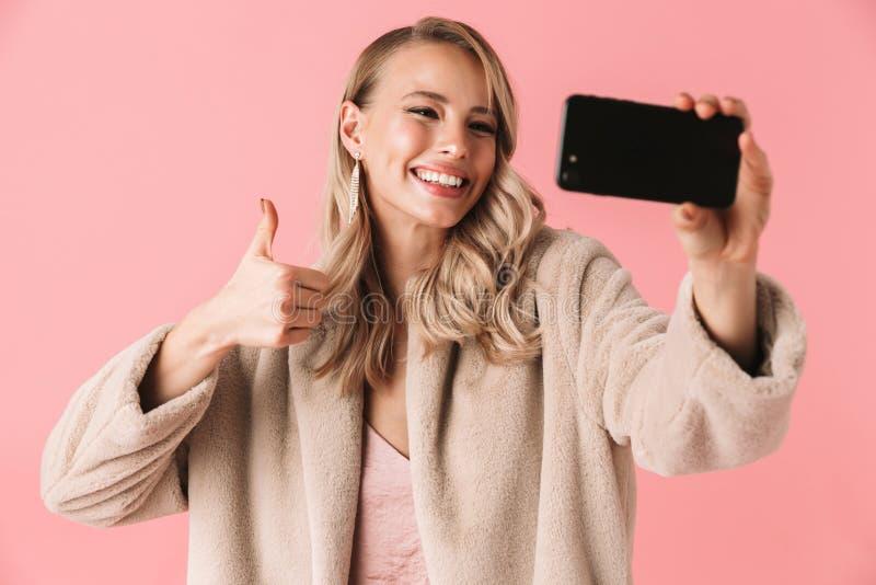 Levantamento bonito novo da mulher isolado sobre o fundo cor-de-rosa da parede para tomar um selfie pelo telefone celular fotografia de stock