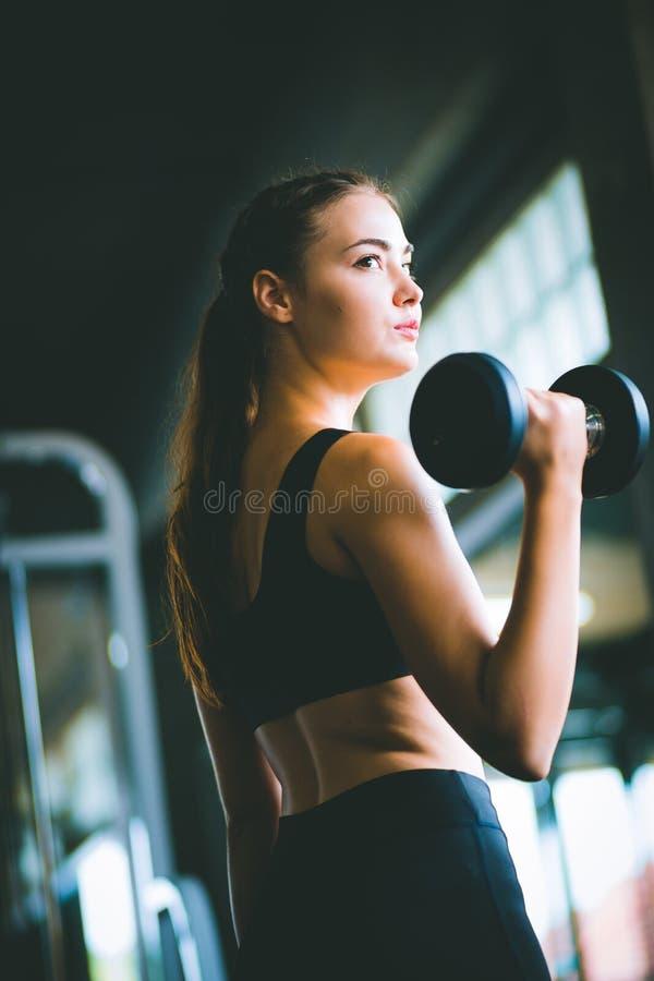 Levantamento caucasiano da jovem mulher bonita apta na câmera no sportswear foto de stock