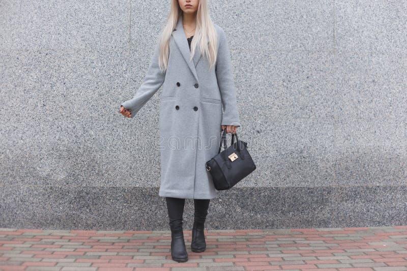 Levantamento da mulher elegante exterior, guardando o saco de couro preto, botas à moda vestindo, revestimento elegante Conceito  imagens de stock