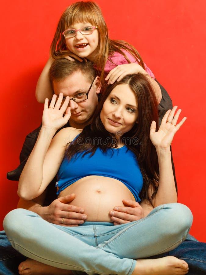 Levantamento da mulher gravida, do homem e da filha foto de stock