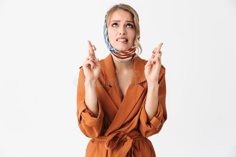 Levantamento de seda vestindo do lenço da mulher bonita loura nova nervosa isolado sobre o fundo branco da parede para fazer o ge fotografia de stock royalty free