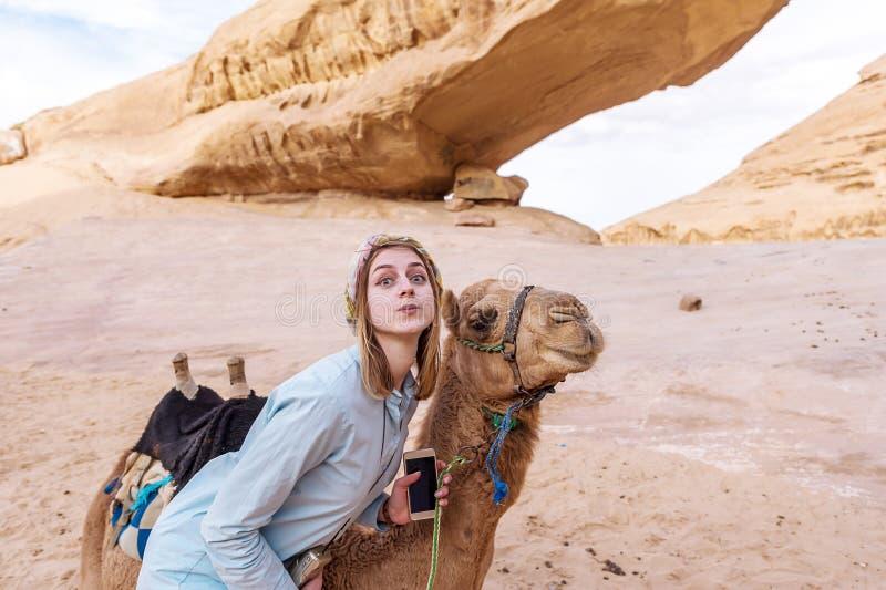 Levantamento de sorriso da jovem mulher com um camelo no meio do deserto de Jordão fotos de stock