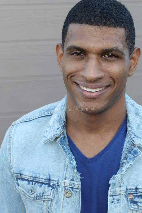 Levantamento de sorriso do homem afro-americano considerável novo isolado no moderno à moda do fundo cinzento fotografia de stock