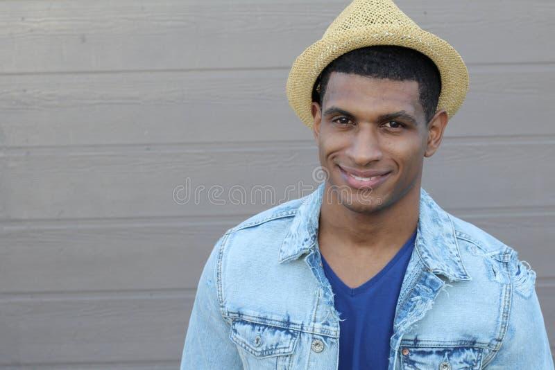 Levantamento de sorriso do homem afro-americano considerável novo no moderno à moda do fundo cinzento fotografia de stock royalty free