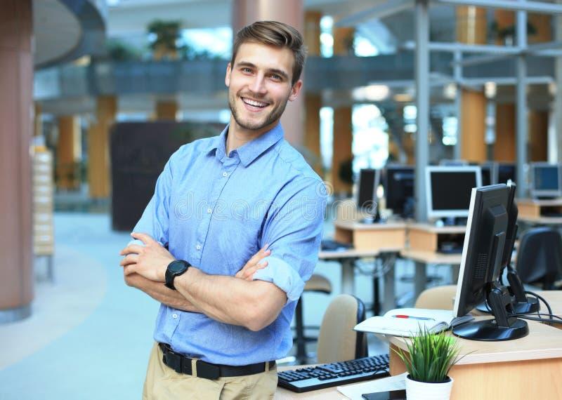 Levantamento do homem novo seguro e positivo no escritório profissional do local de trabalho com espaço imagens de stock