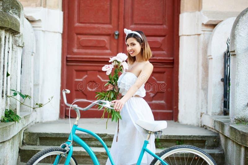 Levantamento fêmea bonito com as flores perto da bicicleta azul na frente do patamar bonito fotografia de stock royalty free