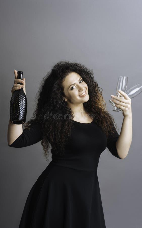 Levantamento fêmea bonito com a garrafa do vinho fotografia de stock royalty free