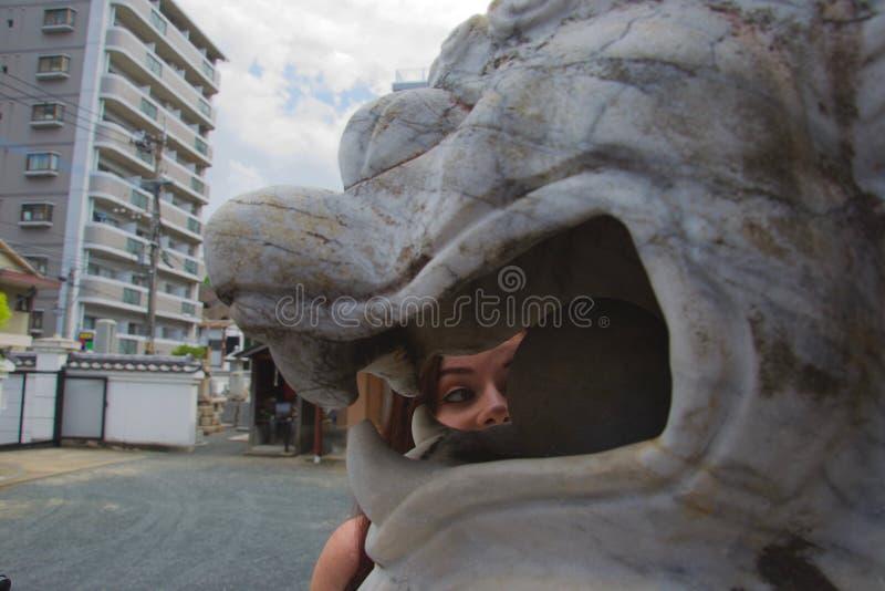 Levantamento fêmea caucasiano do turista, olhando através da boca de uma estátua de mármore branca do dragão em Japão fotos de stock