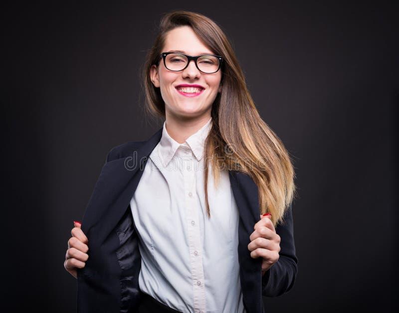 Levantamento fêmea de sorriso bonito no terno formal foto de stock