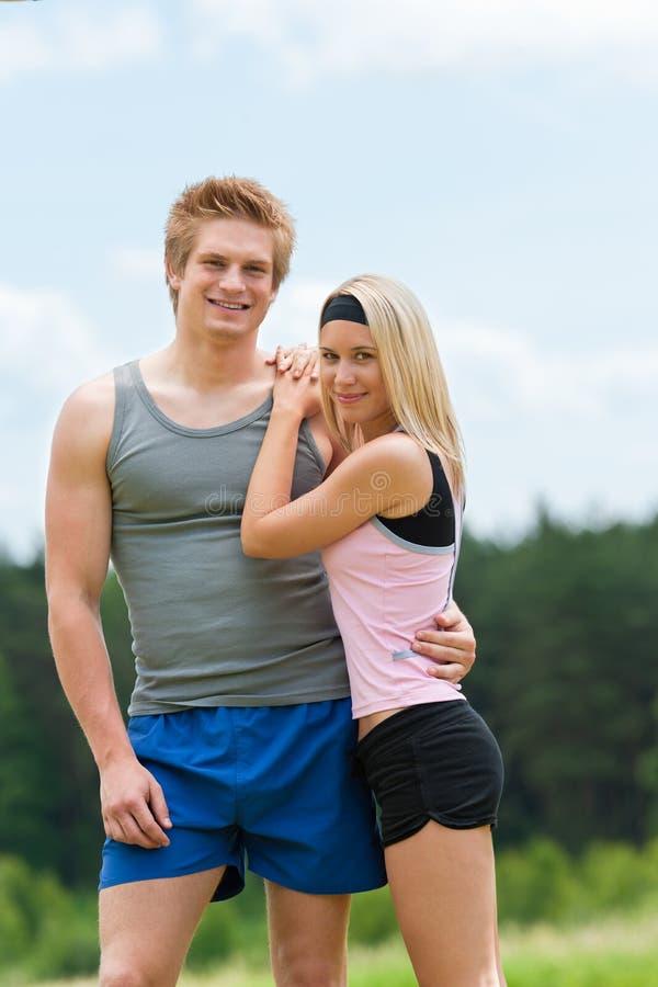 Levantamento feliz dos pares novos Sportive no campo imagens de stock royalty free