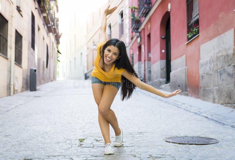 Levantamento feliz e entusiasmado da mulher latin atrativa nova na cidade europeia urbana moderna imagem de stock royalty free