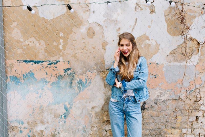 Levantamento louro bonito da mulher sensual na frente da parede de pedra velha Modelo novo que fala no telefone fora com imagem de stock royalty free