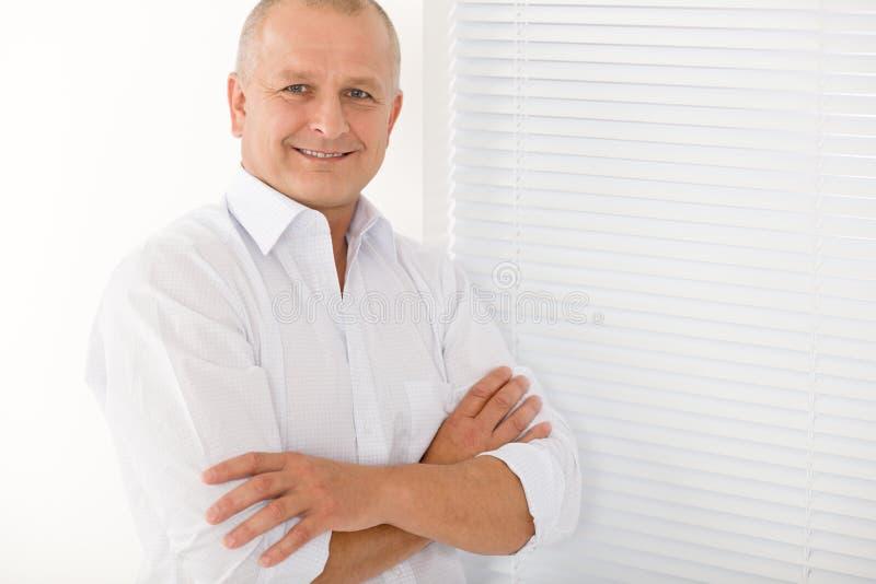 Levantamento maduro dos braços da cruz do sorriso do homem de negócios fotos de stock