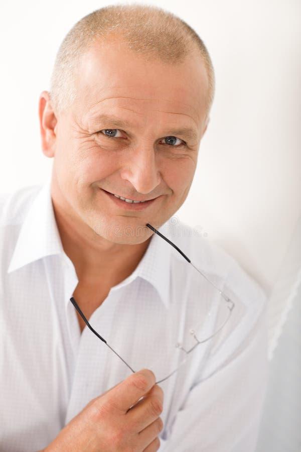 Levantamento maduro dos vidros da preensão do sorriso do homem de negócios imagens de stock royalty free