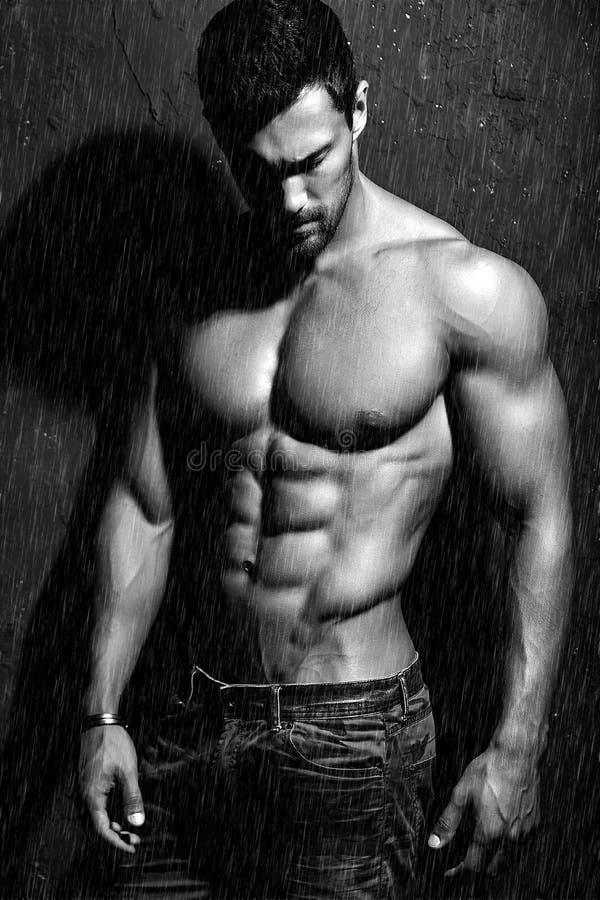 Levantamento modelo da aptidão atlética considerável saudável forte do homem perto da obscuridade - parede cinzenta imagens de stock