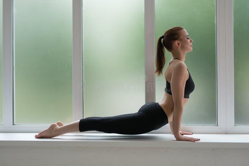 Levantamento modelo da aptidão no tiro do estúdio do peitoril da janela fotos de stock royalty free