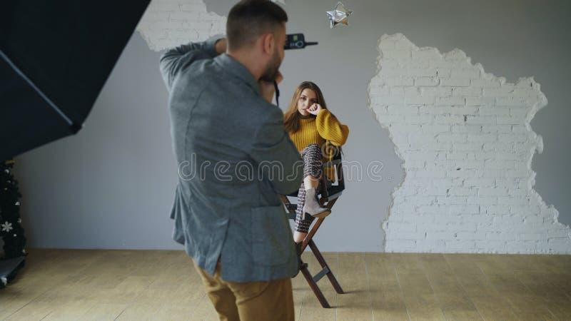 Levantamento modelo da mulher bonita nova para o fotógrafo quando disparar com uma câmara digital no estúdio da foto dentro imagem de stock
