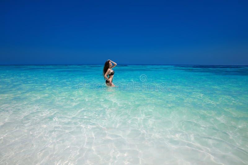 Levantamento modelo do biquini 'sexy' moreno na superfície da onda do mar, vagabundos do verão fotos de stock
