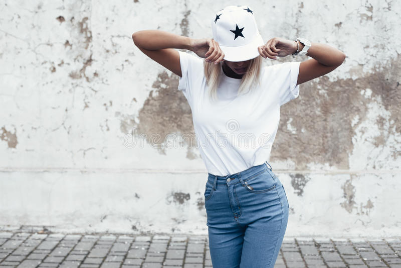 Levantamento modelo no tshirt liso contra a parede da rua fotos de stock
