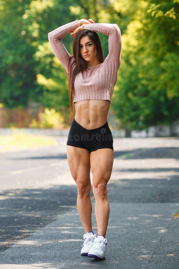 Levantamento muscular bonito da menina exterior Mulher atlética 'sexy' com quadriláteros grandes imagem de stock