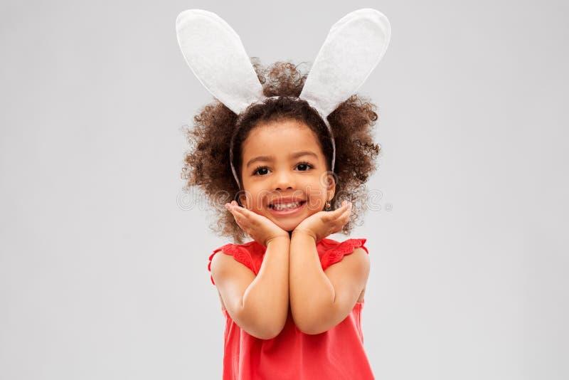 Levantamento vestindo das orelhas do coelhinho da Páscoa da menina feliz fotografia de stock royalty free