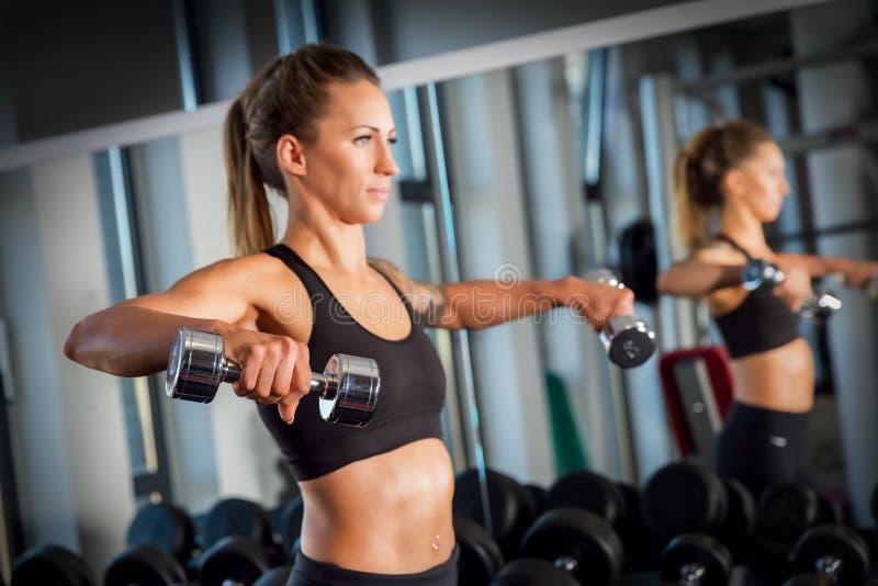 Levantamiento de pesas atractivo de la mujer en el gimnasio foto de archivo