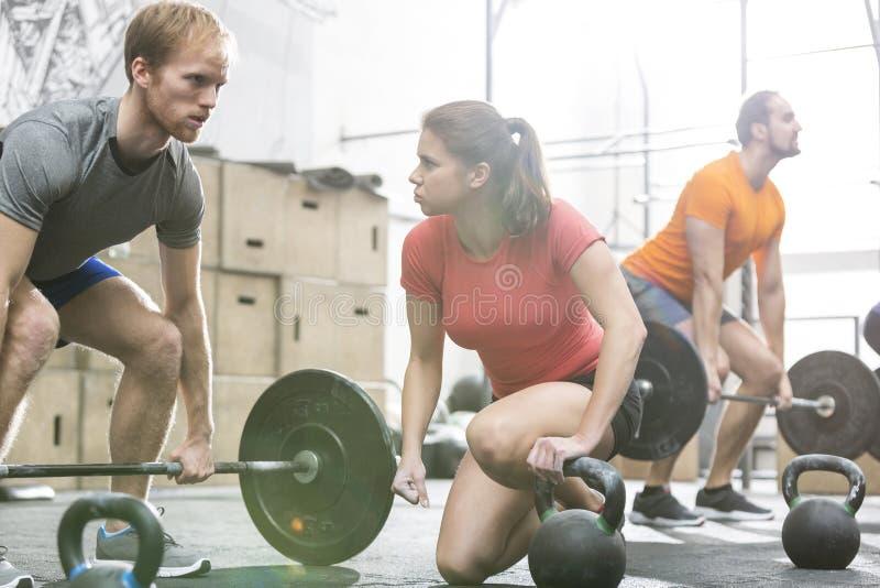Levantamiento de pesas de la gente en gimnasio del crossfit fotografía de archivo libre de regalías