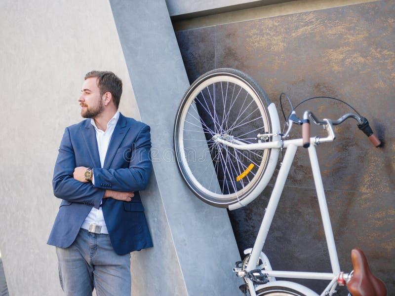 Levantan al hombre de negocios que mira al lado, al lado de la bici en sus piernas traseras foto de archivo libre de regalías