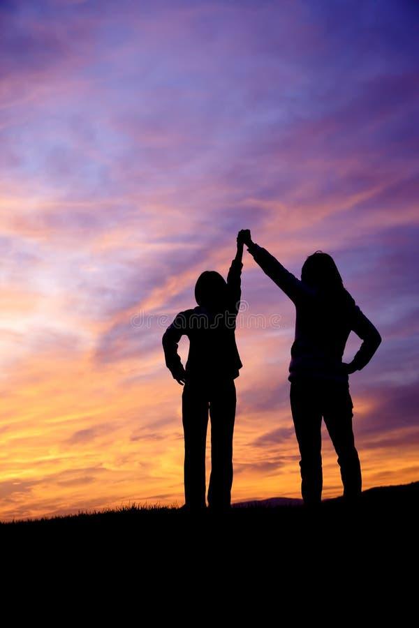 Levantando as mãos no por do sol. fotografia de stock royalty free