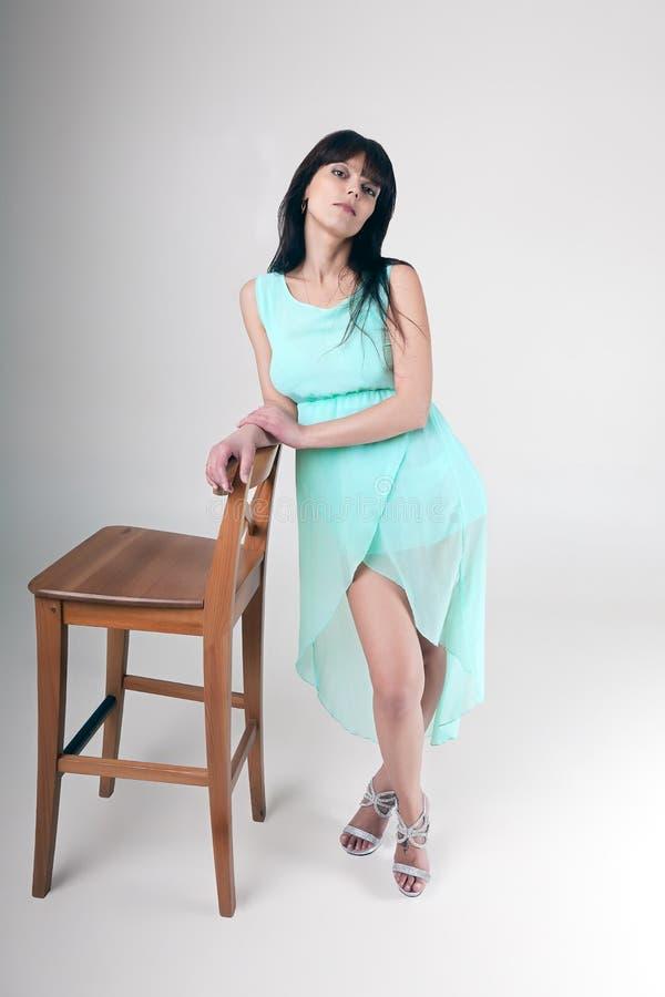 Levantando a morena que está ao lado da cadeira no estúdio fotografia de stock royalty free