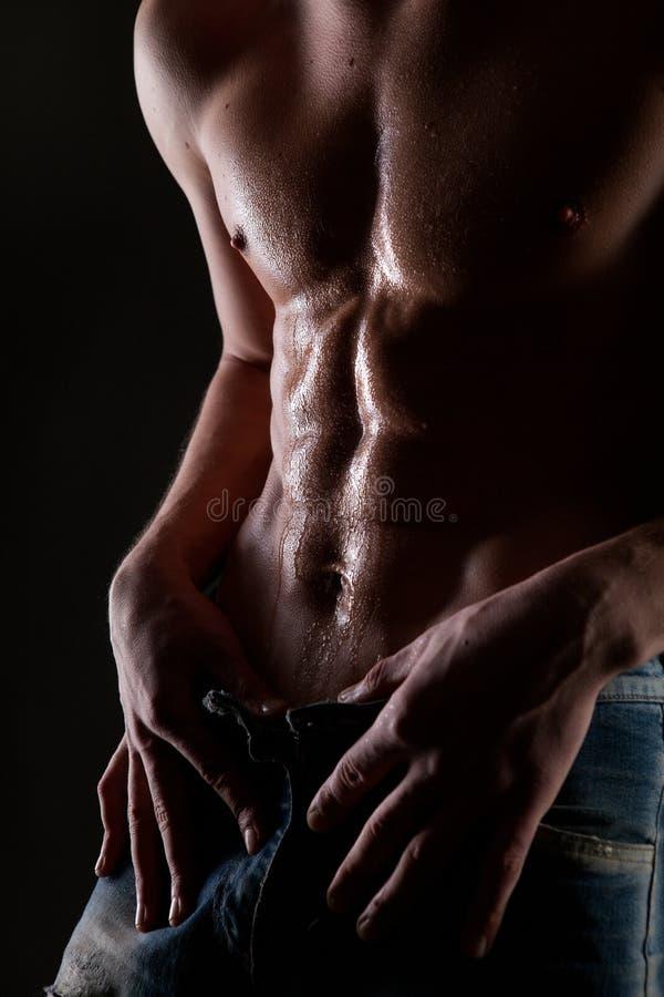 Levantar o homem despido muscular com corpo na água deixa cair imagem de stock