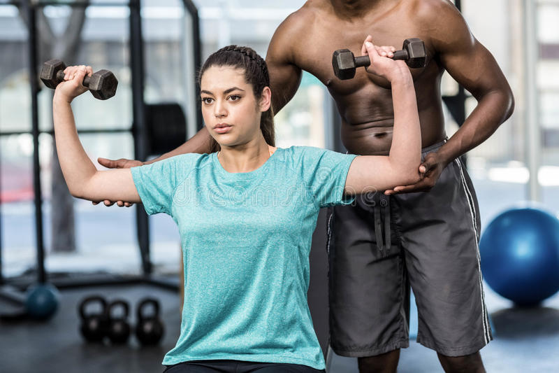 Levantar peso atlético da mulher ajudado pelo instrutor imagens de stock