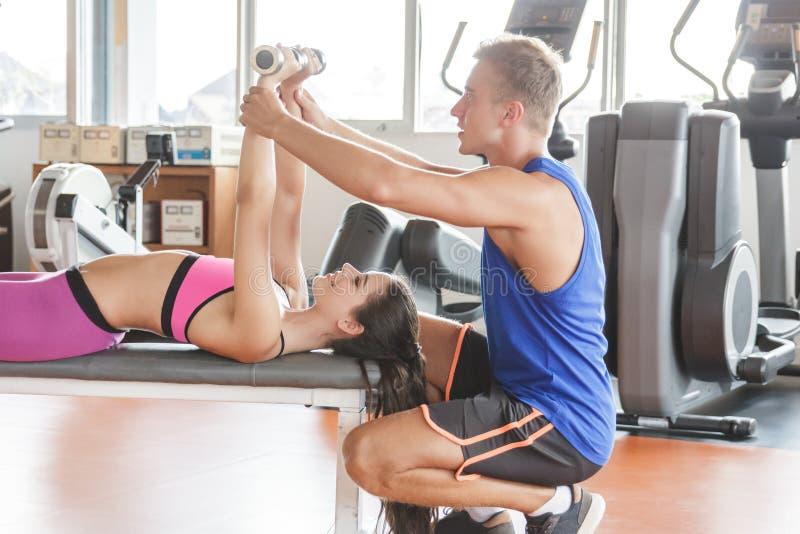 Levantar peso do exercício da jovem mulher ajudado por seu instrutor fotografia de stock royalty free