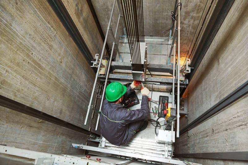 Levante al maquinista que repara el elevador en eje de elevaci?n imágenes de archivo libres de regalías